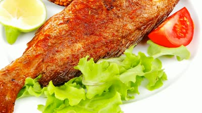 stock-footage-main-course-roasted-sea-fish-on-plate-with-tomatoes-lemon-and-spices