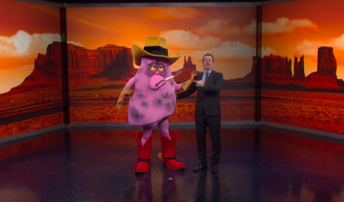 John Oliver with Jeff the disease lung who looks like a cowboy with his hat and boots.