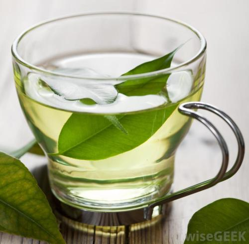 cup-of-green-tea-with-leaves-on-wood