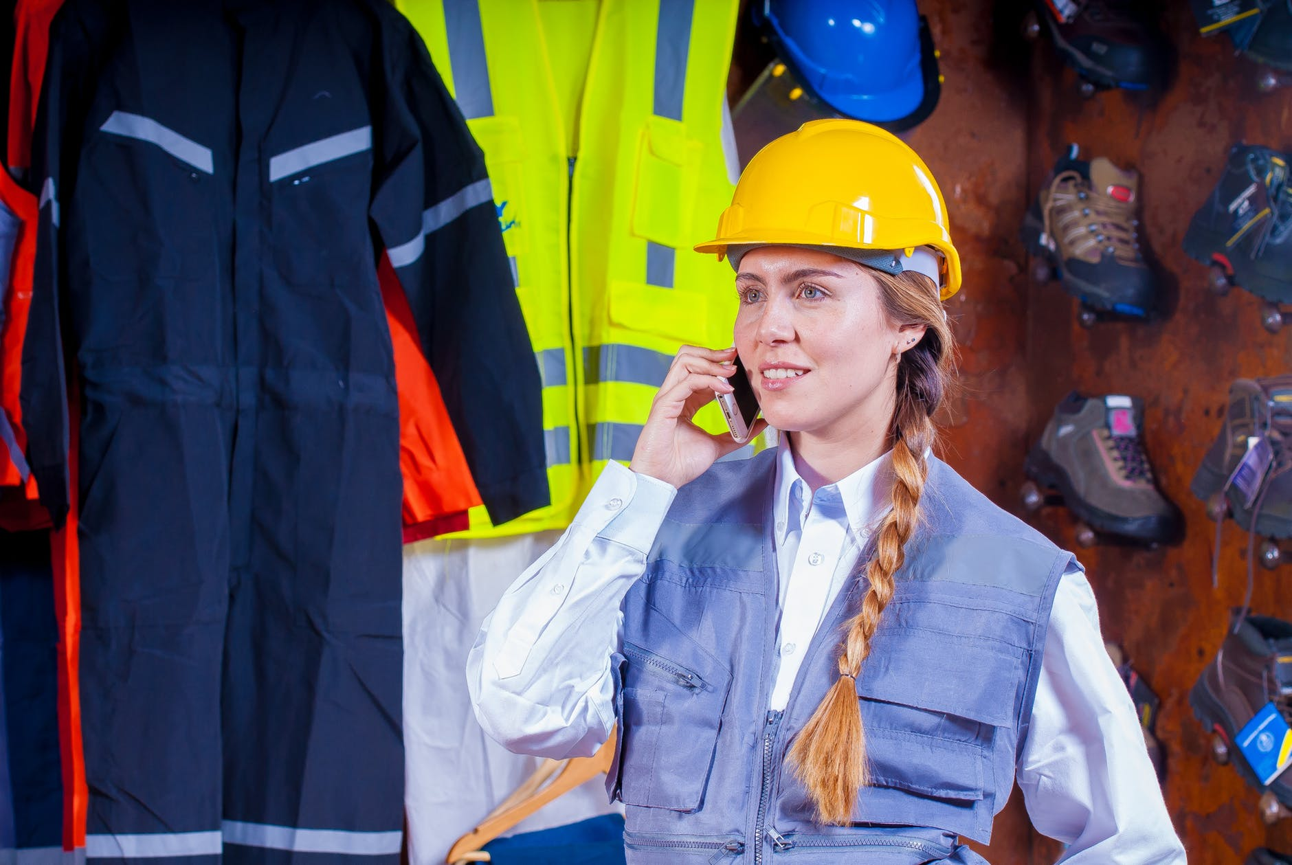 woman in gray vest with yellow hard hat inside room