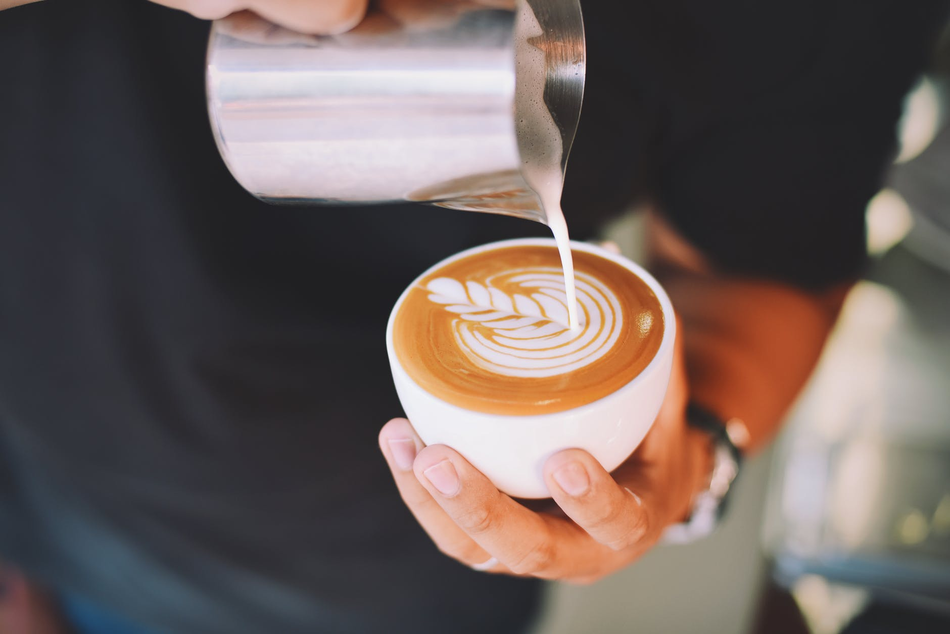 close up of hand holding cappuccino