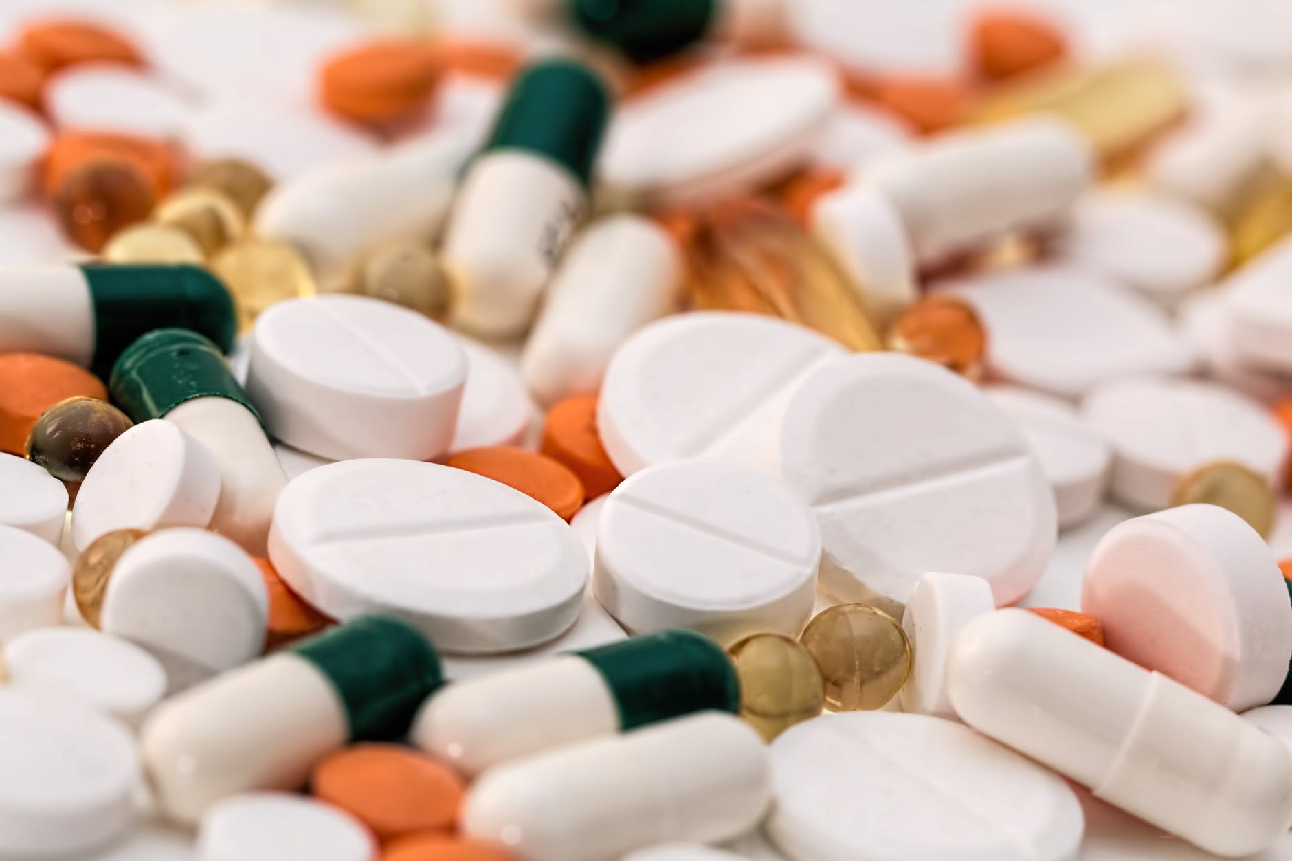 bunch of white oval medication tablets and white medication capsules