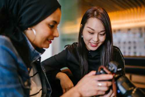 woman looking to woman holding dslr camera
