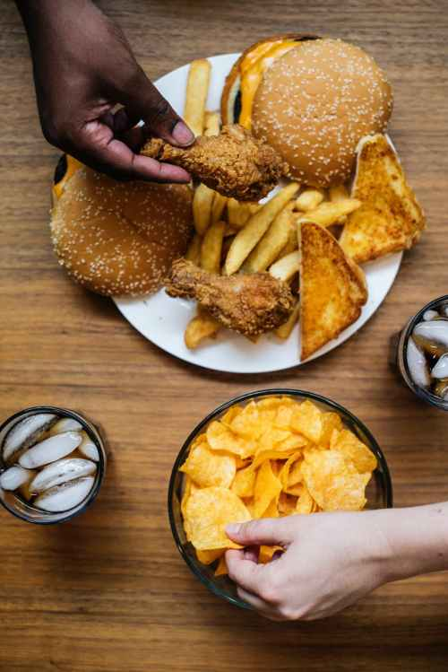 two people holding chips and fried chicken