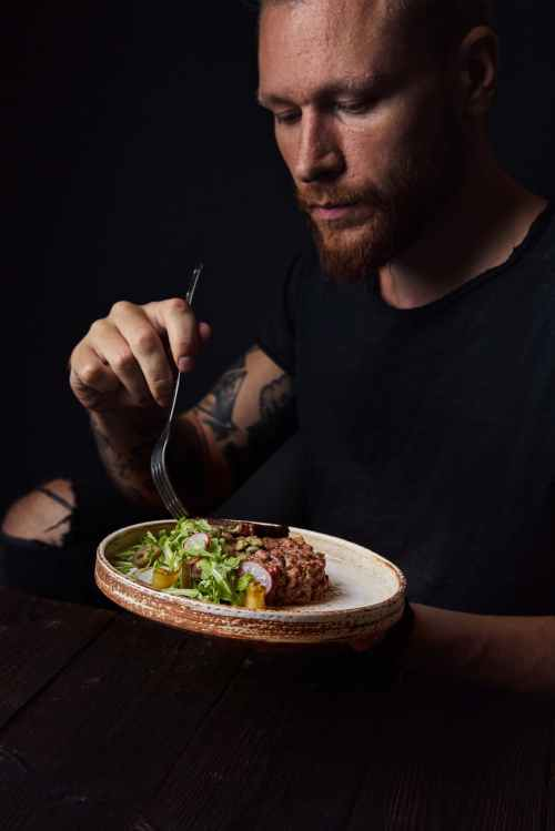 man eating meat with vegetables