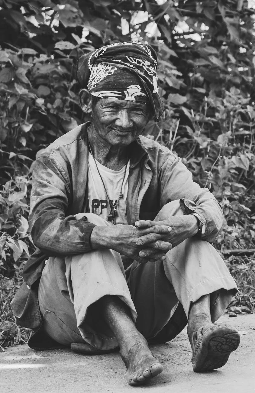 grayscale photo of old man sitting on the ground near plants