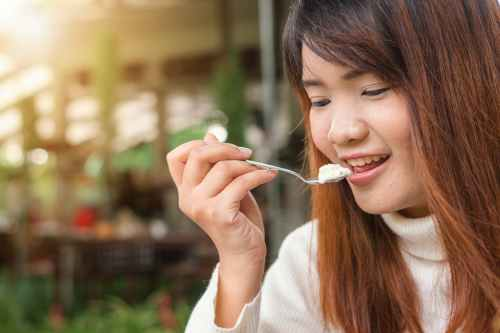 woman holding spoon trying to eat white food