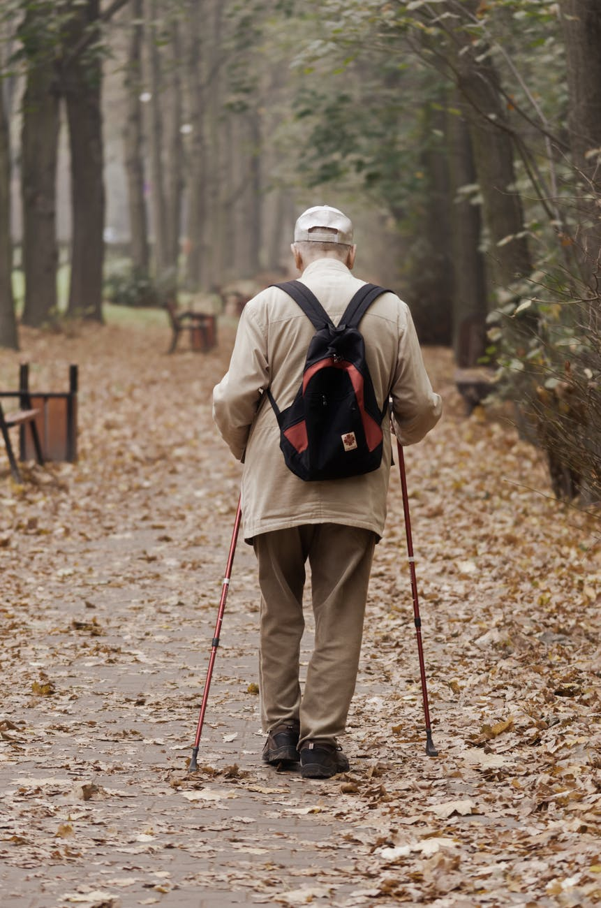man carrying backpack while walking on a paved pathway