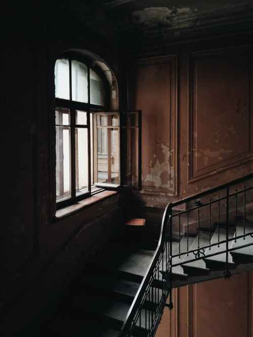 black and brown stairs beside window