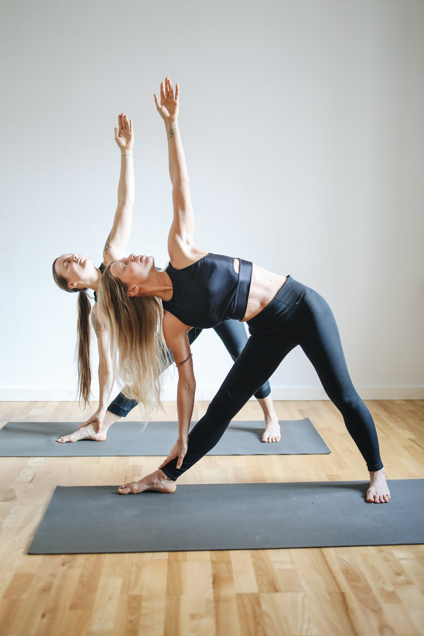 two women in black tank tops and black leggings doing yoga
