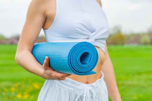 woman standing and holding blue yoga mat